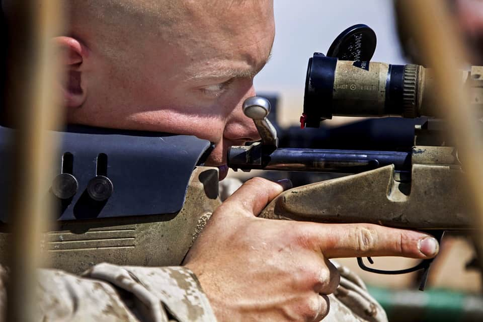 Image showing shooter aiming through a rifle scope. Could be one or both eyes open to aim.