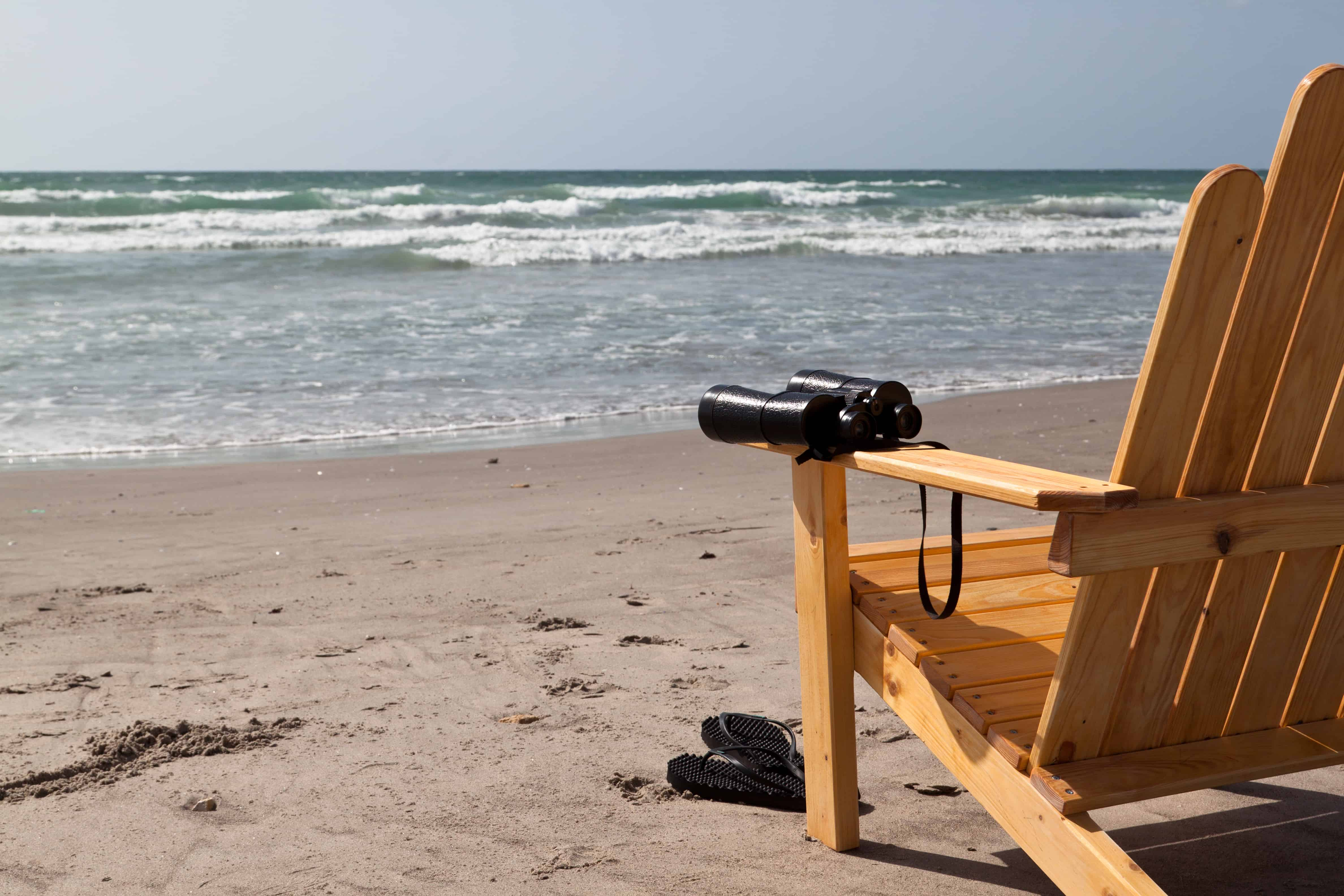 Environment watching with binoculars on the beach